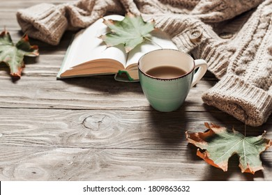 Autumn morning coffee. A cup of coffee on a wooden table and a warm sweater on a background of autumn leaves. Still life concept. Copy space.