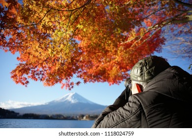 In autumn mornning ,old photograper wait for sunrise to shooting fuji mountain photo , maple leaf , kawaguchiko lake