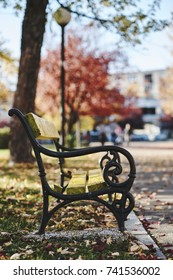 Autumn motives Yellow Leaves on the bench with street lamp in background, side view, vertical