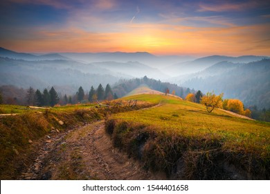 Autumn mountain  landscape with mist at dawn. Vibrant colorful sky over mountain hills with picturesque country road. Fall background.