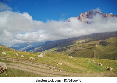 Autumn mountain landscape. Scenic view of the alpine pasture and Mount Erydag. Red rock Erydag (3925 m) - popular place of mountaineering. Russia, North Caucasus, Dagestan, Dokuzparinsky District