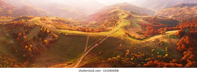 Autumn mountain panorama. Sunny landscape with meadow and colorful forest. Red, Yellow, Orange trees on hillsides. National Natural Park Synevyr, Carpathians, Ukraine, Europe.
