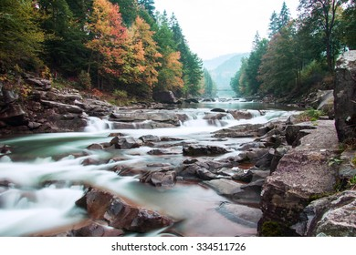 Autumn mountain river view with waterfall and bridge