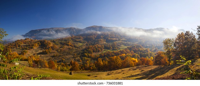 Autumn in the mountains with fog and colorful trees - rural panoramic landscape