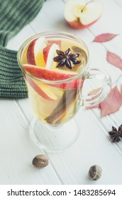 Autumn mulled wine or gluhwein based on white wine with rum, apple and spices cinnamon sticks, star anise, nutmeg, cardamom and clove on white wooden background. Seasonal beverages recipe.