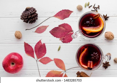 Autumn mulled wine or gluhwein based on red wine with orange, apple and spices cinnamon sticks, star anise, nutmeg, cardamom and clove on white wooden background. Seasonal beverages recipe. Top view.