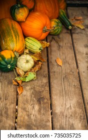 Autumn nature concept. Fall vegetables on wooden texture background. Yellow and orange pumpkin, green squash and fall leaves. Thanksgiving background
