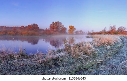 Autumn nature landscape of frosty november morning on river shore with hoarfrost on grass and trees. Calm scenery autumn with red and yellow leaves on branches of tree on river bank