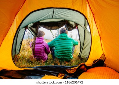 Autumn nature lifestyle, back view of man and woman warm up, relaxing, drinking hot tea near tent outdoors on camping travel. Hiking couple wearing green and purple down jacket enjoying fall season.