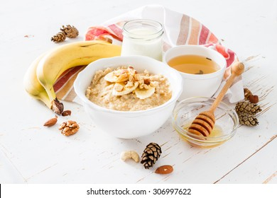 Autumn oatmeal in white bowl banana honey yogurt white wood background