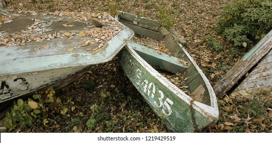 Autumn. Old abandoned boats on the shore, covered with autumn leaves. Concept of oblivion