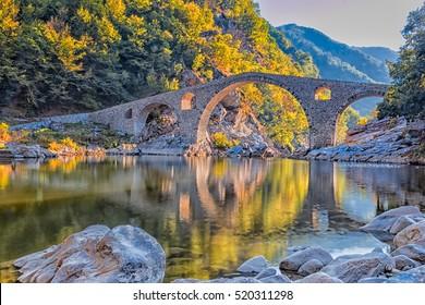 In autumn old stone bridge near Ardino, Bulgaria