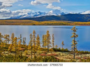 Autumn on Jack London's lake. Mountains in snow. Kolyma