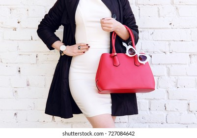Autumn outfit. Woman in black coat hold red handbag in hand. Stylish accessory