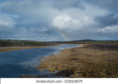 Autumn panorama with lake and forest and rainbow