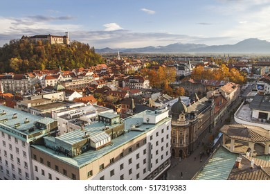 Autumn panorama of Ljubljana Castle and adjacent historical core of the city, surrounded by mountains covered by snow. Fall in the city. Slovenia, Europe.