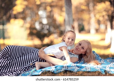 autumn park Mother and daughter lying on the ground playing