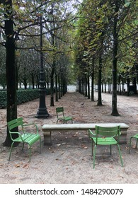 Autumn park in Paris: valley with green chairs and bench