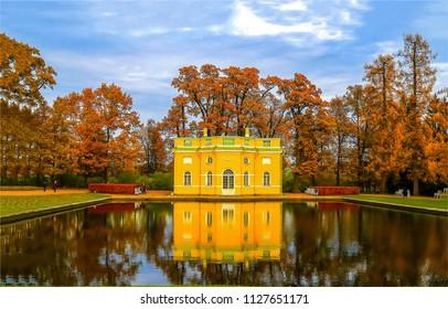 Autumn park pond reflection landscape. Yellow house at autumn park pond panorama. Autumn park pond mansion view