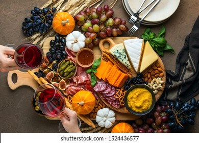 Autumn party easy snack board concept, view from above on snack platter and two hands holding wine glasses