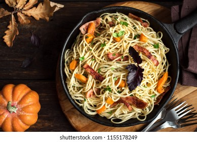 Autumn pasta with pumpkin and bacon in cast iron pan. Homemade spaghetti pumpkin pasta on wooden, copy space. Autumn food.
