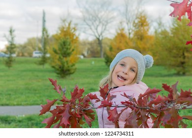 Autumn photo of laughing little girl with red japanese maple branch. Autumn day