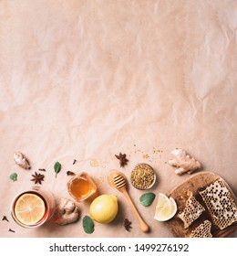 Autumn picnic. Herbal tea, honey and bee products, apple, lemon, calendula, spices on craft paper background. Immune system support with alternative medicine. Top view, copy space.