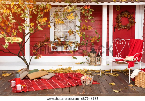 Autumn picnic on the terrace. Red plaid, basket with apples and thermos with hot drink. Veranda of countryside house in autumn season.