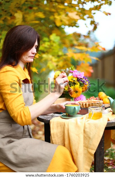 Autumn picnic. Woman in yellow dress and linen apron drinks tea from cup at wooden table in garden. Beautiful kettle, tablecloth, honey with spoon, apple pie, harvest, persimmon, grapes, maple leaf.