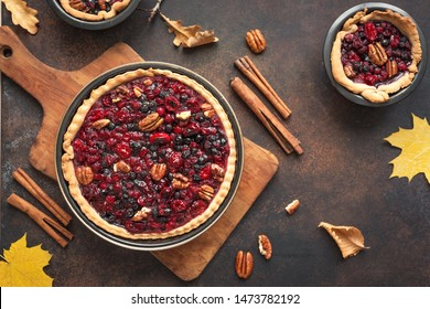 Autumn Pies on rustic background, top view, copy space. Homemade seasonal pastry - berries and pecan pies or tarts for Thanksgiving and autumn holidays.