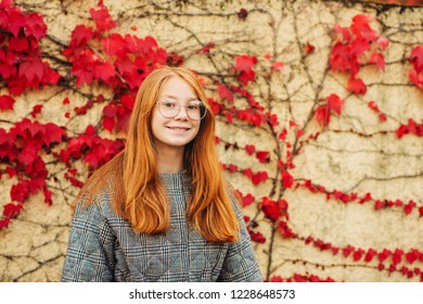 Autumn portrait of adorable red-haired preteen girl girl check jacket and glasses, posing next to wall with red ivy leaves, fall fashion for kids