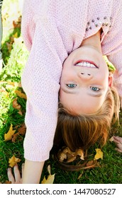 Autumn portrait of adorable smiling little girl child standing upside down on grass and having fun outdoors