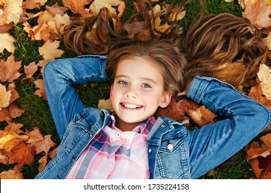 Autumn portrait of adorable smiling little girl child preteen lying in leaves in the park outdoors
