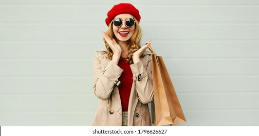 Autumn portrait of attractive smiling woman with shopping bag wearing a coat, red french beret over gray background