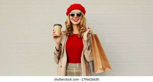 Herbstporträt einer attraktiven jungen Frau mit Einkaufstasche und Kaffeetasse mit rotem französischem Beet auf grauem Hintergrund