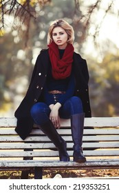 Autumn portrait of beautiful blonde girl in black coat and red scarf
