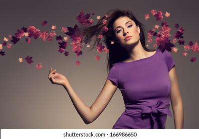 autumn portrait of beautiful woman wearing purple dress against maple leaves