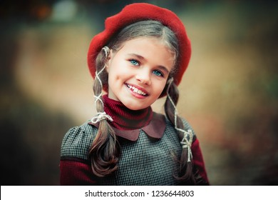 Autumn portrait of a beautiful young schoolgirl in red beret and braid hairs with books . Tenderness positive child with bright smile enjoying nature in park.