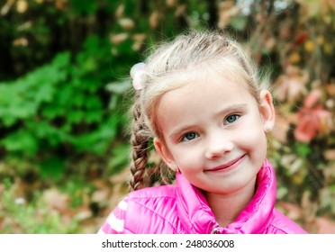 Autumn portrait of cute smiling little girl outdoor