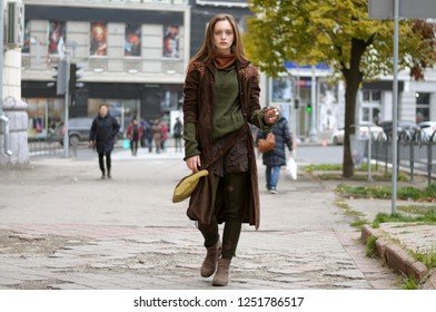 Autumn portrait of a girl who goes on the sidewalk. She is dressed in a boho style: brown coat, yellow bag, green sweater, shorts and torn stockings