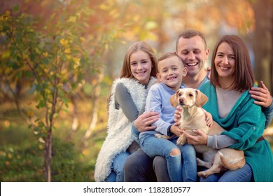 Autumn portrait of happy family with dog having fun outdoors