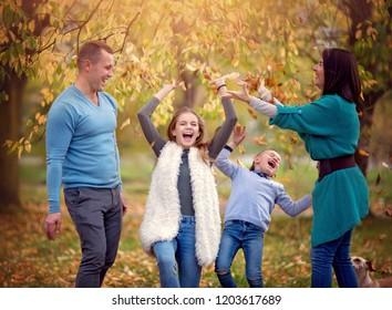 Autumn portrait of happy family having fun outdoors