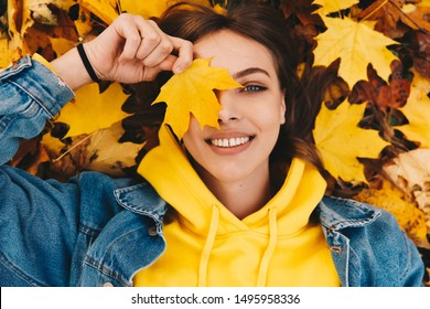Autumn portrait. Happy girl in yellow hoodie and jean jacket is playing with leaf, looking at camera and smiling while lying on the ground in the park; top view