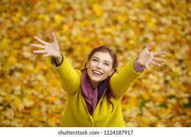 Autumn portrait of a happy smiling girl with purple hair dressed in a yellow coat, pulling her hands up against a background of yellow, red and orange leaves while walking in the park.European woman