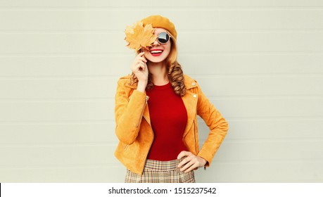 Autumn portrait happy smiling woman holding in her hands yellow maple leaves covering her eye over gray wall background