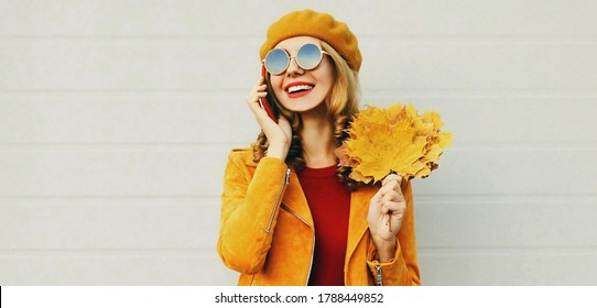 Autumn portrait of happy smiling woman with yellow maple leaves calling on smartphone wearing french beret over gray background
