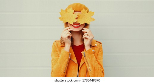 Autumn portrait of happy smiling woman covering her eyes with yellow maple leaves over gray background