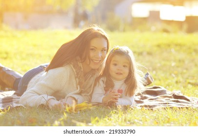 Autumn portrait mother and child smiling on the grass