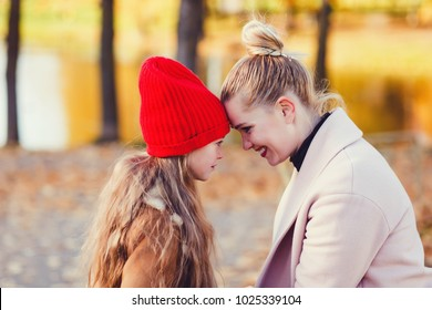 autumn portrait of smiling mother and daughter in the park. the concept of love and care