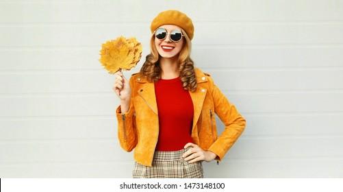 Herbstportrait lächelnde Frau, die gelbe Ahornblätter mit französischer Beete hält, auf der Straße auf grauem Hintergrund